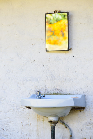 Outdoor sink on a white wall, mirror reflecting bright orange flowers photo