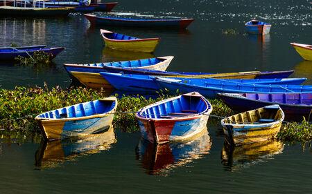 still water: Colorful barques on Fewa Lake in Pokhara, Nepal Stock Photo