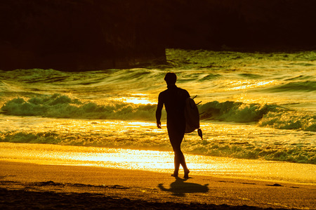 Surfer walking on the beach in the evening light, cross processed effect photo