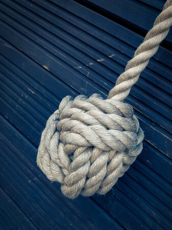 knotted: Nautical knot on a blue wooden background