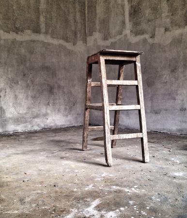stepladder: Wooden stepladder in a concrete room
