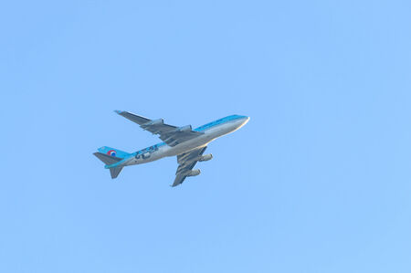 underneath: LONDON, UK - CIRCA FEBRUARY 2011: A Korean Air Boeing 747 is flying over London.
