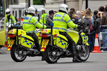 police helmet: LONDON, UK - CIRCA JUNE 2012: Two police officers on their motorbikes.