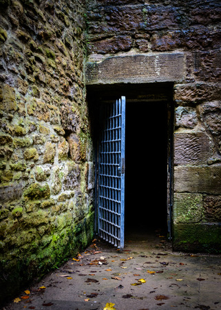 Opened prison door in an old castle Stock Photo