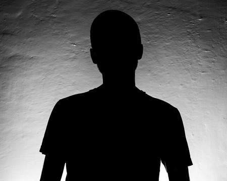 Silhouette portrait of a young man against a wall Stock Photo