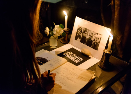 weekly: KATHMANDU, NEPAL - JANUARY 11, 2015: Woman signing the condolences book at  the Caf des Arts gathering in tribute to the victims of the terrorist attacks in Paris.