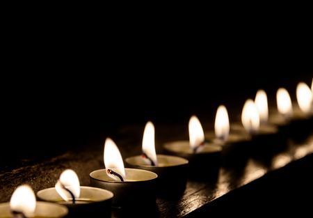 Aangestoken kaarsen in een rij in de nacht Stockfoto