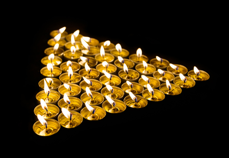 memorial candle: Triangle made of burning candles at night Stock Photo