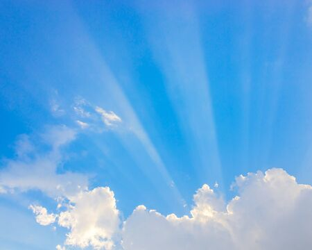 Los rayos del sol pasan a través de las nubes y el cielo azul Foto de archivo