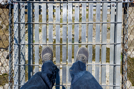 foot bridges: Looking down on a suspension bridge over a river in Nepal