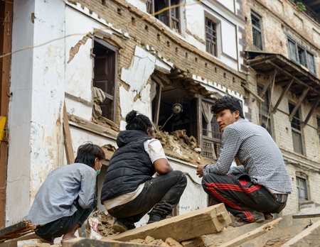 squatting down: KATHMANDU, NEPAL - APRIL 26, 2015: Three young men squatting down on a pile of rubble at Durbar Square which was severly damaged after the major earthquake on 25 April 2015. Editorial