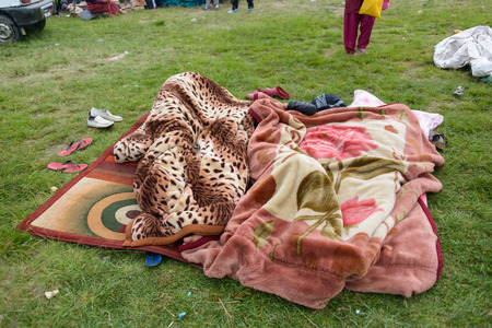under ground: KATHMANDU, NEPAL - APRIL 26, 2015: People sleeping under blankets on an open ground at Chuchepati on the morning after the 7.8 earthquake on 25 April 2015.