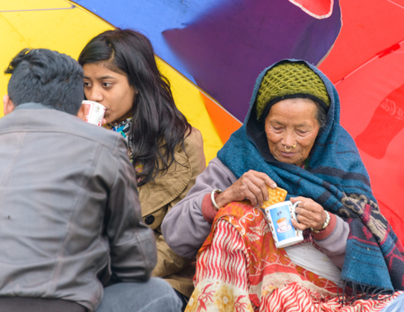 quake: KATHMANDU, NEPAL - APRIL 26, 2015: People drinking tea on an open ground at Chuchepati after their first night outside after the 7.8 earthquake on 25 April 2015. Editorial