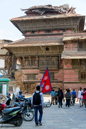 quake: KATHMANDU NEPAL  MAY 14 2015: A man carries a large Nepal flag on Durbar Square a UNESCO World Heritage Site.