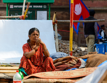 earthquakes: KATHMANDU NEPAL  MAY 14 2015: A Nepalese woman sits in a makeshift campsite after two major earthquakes hit Nepal in the past weeks.
