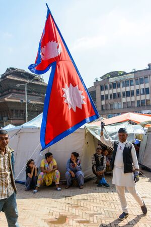 the aftermath: KATHMANDU, NEPAL - MAY 14, 2015: A man carries a large Nepal flag on Durbar Square, a UNESCO World Heritage Site.