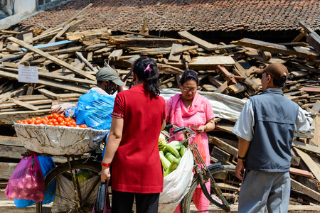 the aftermath: KATHMANDU, NEPAL - MAY 14, 2015: A man sells vegetables on Durbar Square which was partially destroyed after two major earthquakes hit Nepal in the past weeks.