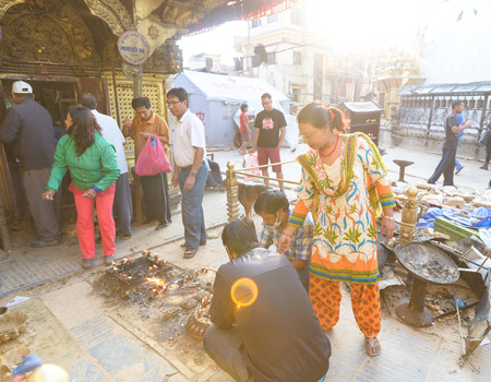 severely: KATHMANDU, NEPAL - MAY 22, 2015: People praying at Swayambhunath which was severely damaged after two major earthquakes hit Nepal on April 25 and May 12, 2015.