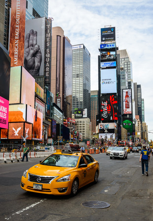 time square: NEW YORK, USA - AUGUST 7, 2015: A yellow cab drives past Times Square.