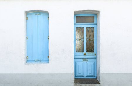 white window: Detail of a white house with blue shutters and door in Noirmoutier-en-lle, France