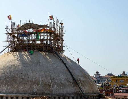 bodnath: KATHMANDU, NEPAL - OCTOBER 3, 2015: After experiencing strucural damages due to the April 25th earthquake, the top of Boudhanath stupa is being dismantled. It will be reconstructed as before. Editorial