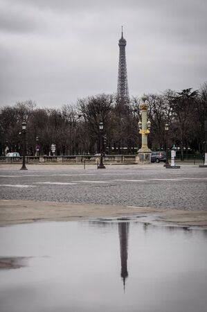 concorde: The Eiffel Tower and his reflection in a puddle as seen from the Concorde Square in Paris, France. Winter season.