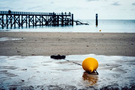 flotation: Orange buoy on a beach, pier in the background in Noirmoutier, France. Film emulation filter applied.