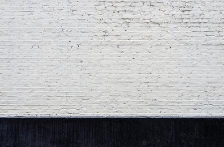 Muro di mattoni bianchi e nero battiscopa tessitura