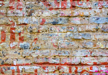wall texture: Grungy brick wall texture with torn posters in Kathmandu, Nepal