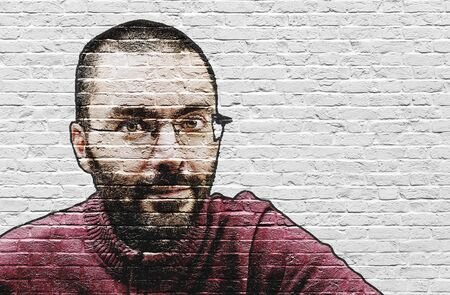grinning: Grinning bearded man in glasses and red sweater with close shave painted on white brick wall Stock Photo