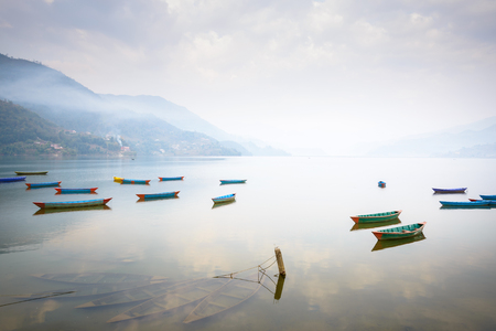 phewa: Boats on Phewa Lake in Pokhara, three sunken ones in the foreground, Nepal.