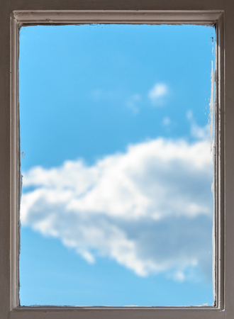 panes: View of a clear sunny blue sky with fluffy white clouds through the wooden frame of an old window in a conceptual image Stock Photo