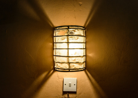 switch: Centered straight on view of illuminated frosted glass flush mount lamp above light switch in dark wall Stock Photo