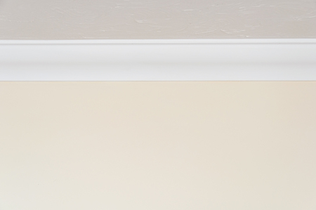 architrave: Close up of white ceiling moulding and light brown wall for background with copy space at top and bottom Stock Photo