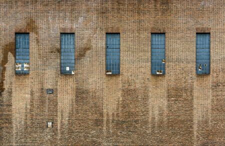 abandoned factory: Old factory brick wall, five windows, some of them broken