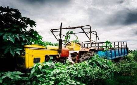industry moody: Abandoned vintage yellow tractor with blue trailer in Nepal