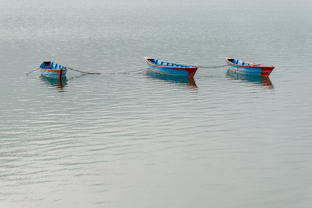 phewa: Three blue small boats on Phewa Lake in Pokhara, Nepal
