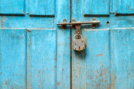 padlocked: Padlock on a blue grungy door in Nepal Stock Photo