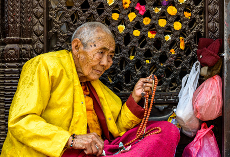 bodnath: KATHMANDU, NEPAL - CIRCA MARCH 2013: Elderly Buddhist nun holding her prayer beads at Boudhanath stupa.