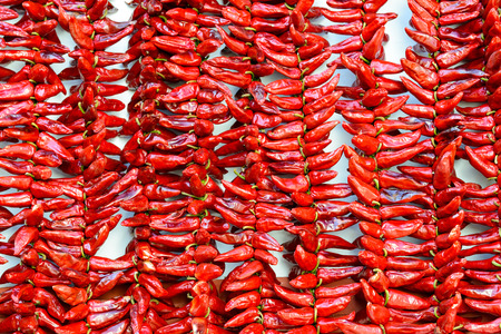 apo: Strings of PDO Espelette chilli peppers drying, France