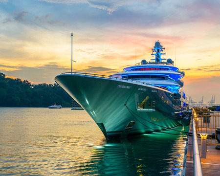docked: Docked green yacht at sunset in Singapore