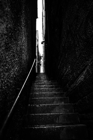 sombre: Narrow stairs between two high walls by a rainy day, black and white