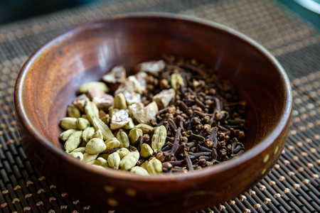 areca: Cardamon, cloves and areca nuts in wooden bowl Stock Photo