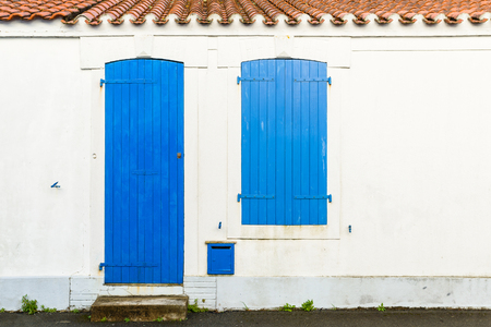 shutter: House facade with blue blinds and door in Noirmoutier island, France