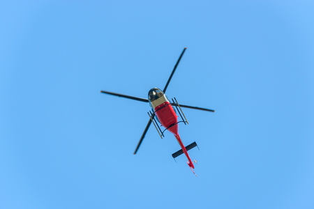 Red and white helicopter in flight against blue sky Stock Photo
