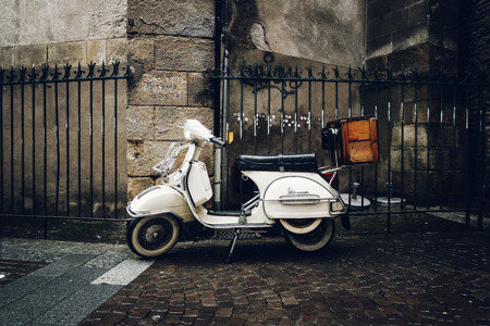 NANTES, FRANCE - CIRCA JANUARY 2018: A vintage Vespa scooter parked in the street by a rainy day. Editorial