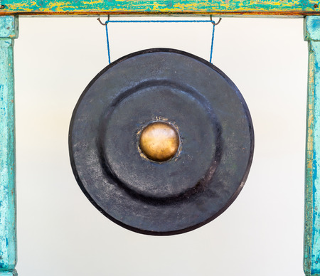 Black and golden traditional Asian gong attached to a green wood frame.