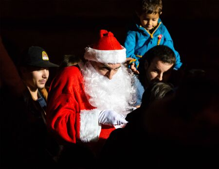 BAYONNE, FRANCE - DECEMBER 15, 2019: A Santa Claus, also known as Father Christmas gives sweets to children.