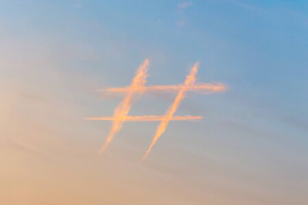 Hashtag sign in sky at sunset, icon made out of contrail clouds. Social media and microblogging concept.