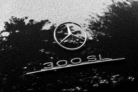 LONDON, UK - CIRCA SEPTEMBER 2011: Black and white closeup shot of Mercedes 300SL logo. Raindrops on the bodywork.